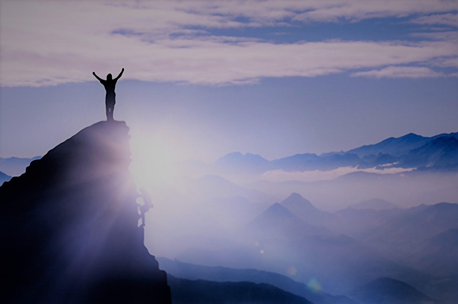 Bergsteiger auf einem Gipfel im Gebirge bei Nebel